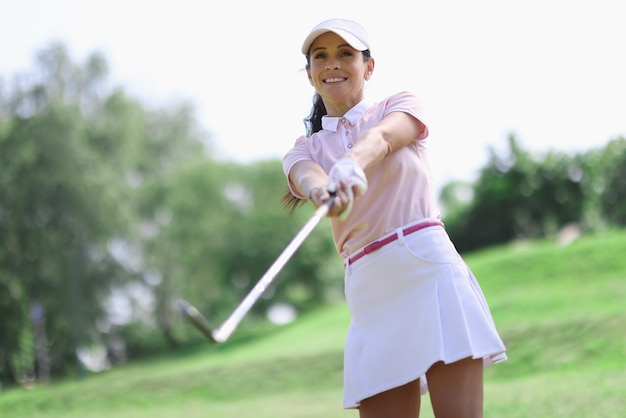 Woman golfer with putter in hand after hitting.