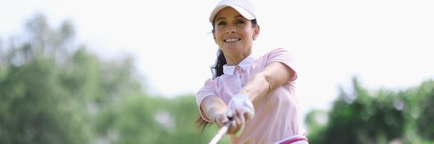 Игрок в гольф женщина с клюшкой в руке после удара