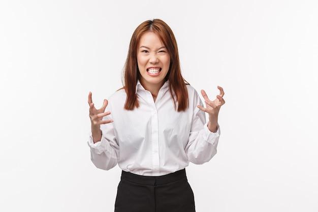 여자는 분노에서 악용 할 것입니다. 화가 화가 아시아 젊은 여성 주먹에 손을 쥐고 모든 분노, 찡그린 공격적, 쳐다 보는 경멸과 증오와 누군가를 펀치 싶어