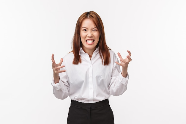 Woman gonna exploit from anger. pissed-off and angry young asian female squeez hands into fists want punch someone with all fury, grimacing aggressive, staring disdain and hate