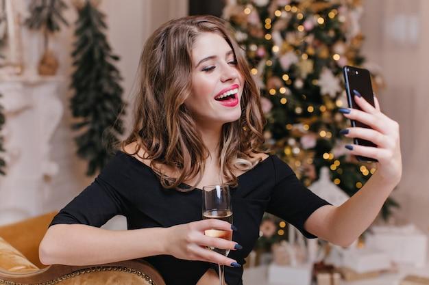 Donna di buon umore festivo parla con i suoi amici tramite videochiamata nel suo telefono e tiene un bicchiere di vino. ritratto di gioiosa modella europea in atmosfera natalizia