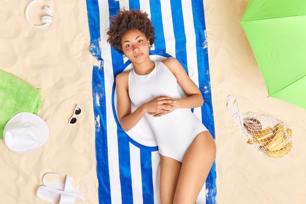 日焼けした女性は赤い顔をしている白いビキニを着ている縞模様のタオルの上に横たわっているさまざまなアイテムに囲まれたビーチで休暇を過ごす長い間日光浴。夏休み