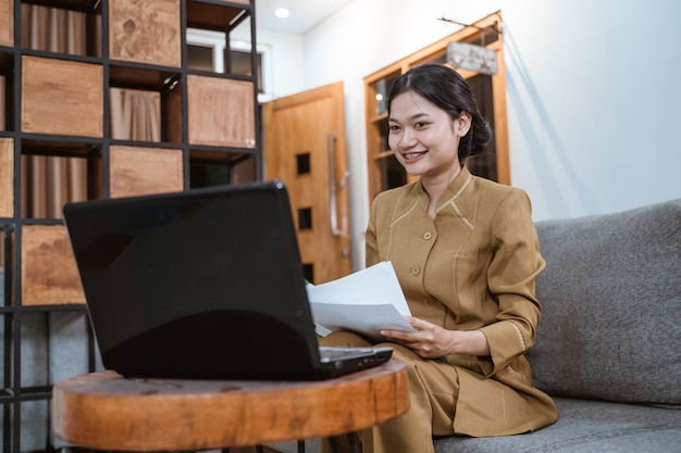 Woman in government uniform holding papers while working from home online using laptop computer