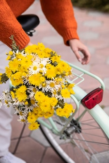 Woman grabbing bicycle with bouquet of flowers outdoors