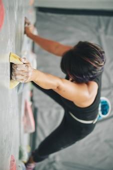 Женщина хватая валун на стене для скалолазания