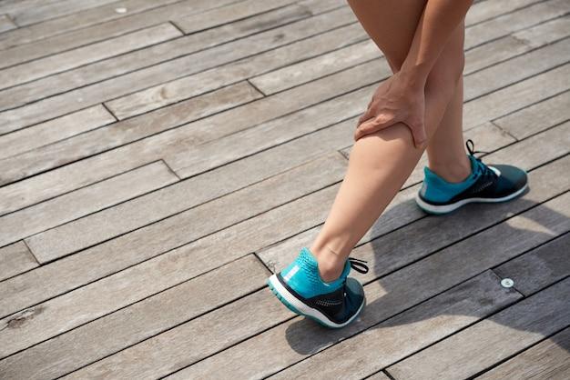 屋外で痛みを伴う脚をつかむ女性