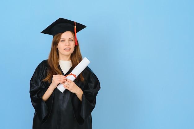 Аспирант женщина в выпускной шляпе и платье, на синем фоне