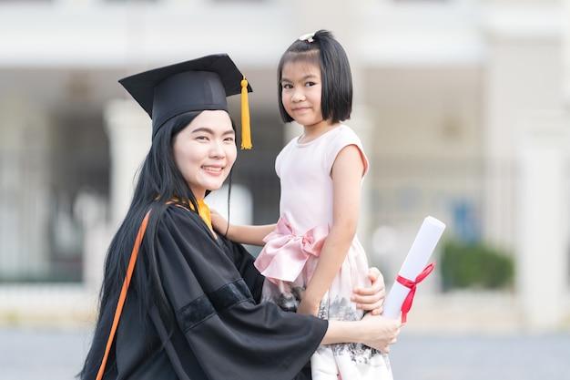 그녀의 졸업식 날에 어린 소녀와 여자 졸업