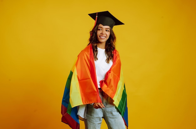 Woman in a graduation hat posing with lgbt rainbow flag on yellow