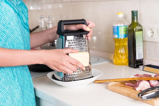 彼女が夕食を調理するときにキッチンカウンターに立っている生の刻んだ肉にレシピを追加するためにチーズのくさびをすりおろす女性