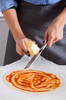 Woman grating the cheese over the homemade pizza bread over the parchment