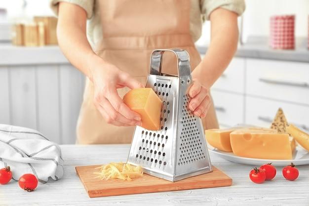 台所のテーブルにチーズをすりおろす女性