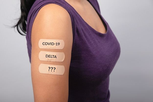 Woman over gray  background showing many plasters on shoulder after coronavirus vaccine, new stamps concept, mutation covid-19