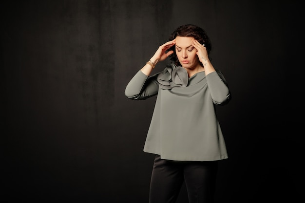 Woman in a gray blouse having a headache, dizzy, touching her temples while closing eyes
