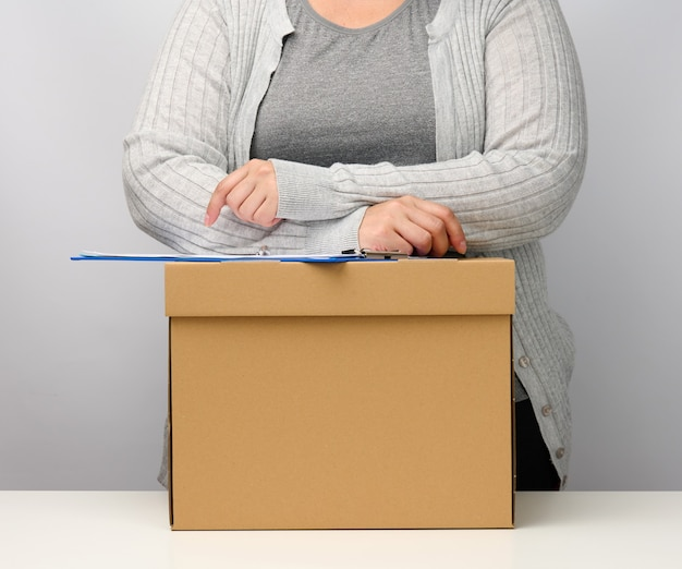 A woman in gray clothes stands near a brown box. the concept of moving, sending and receiving goods. dismissal from work
