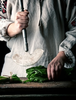 Woman in a gray linen dress is cutting green leaves of fresh sorrel on wooden cutting board