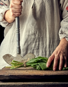 Woman in a gray linen dress is cutting green leaves of fresh sorrel