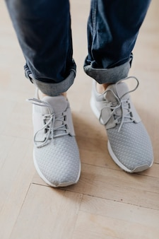 Woman in gray sneakers standing on a wooden floor