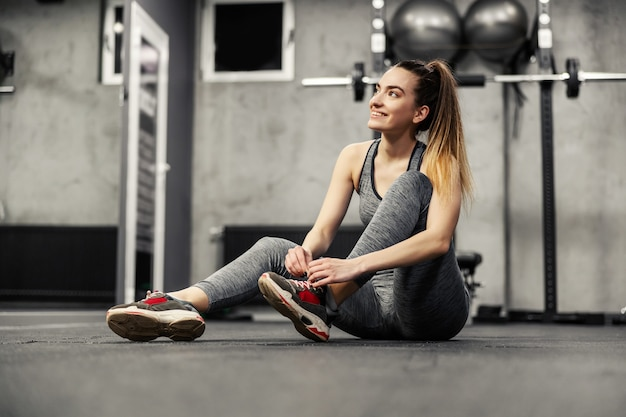 A woman in gray sportswear sits on the floor of an indoor gym and prepares to start training