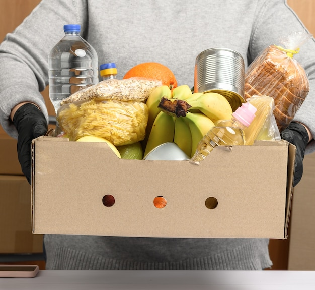 Woman in gray sweater and black gloves holding a cardboard box with groceries, concept of assistance and volunteering, food delivery