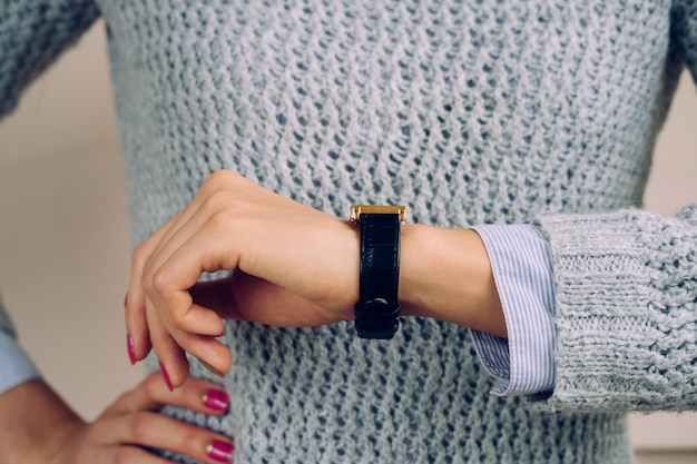 Woman in a gray sweater checks the time on wrist watch close-up