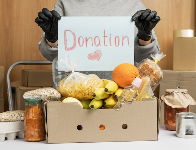 Woman in a gray sweater and gloves is holding a sheet of paper with the inscription donation, on the table there is a cardboard box with food and fruits. volunteering concept
