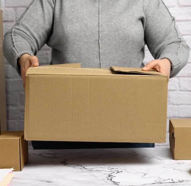 Woman in a gray sweater holding a brown cardboard box, moving, donation