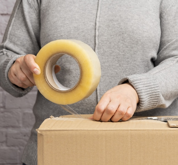Woman in a gray sweater holds a roll of duct tape and packs brown cardboard boxes. moving concept