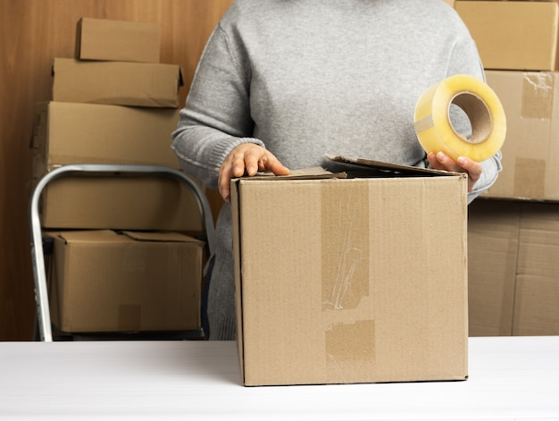 Woman in a gray sweater holds a roll of duct tape and packs brown cardboard boxes on a white table, behind a stack of boxes. moving concept
