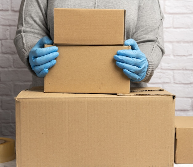 Woman in a gray sweater is packing and blue gloves is holding a stack of brown cardboard boxes, moving, donation