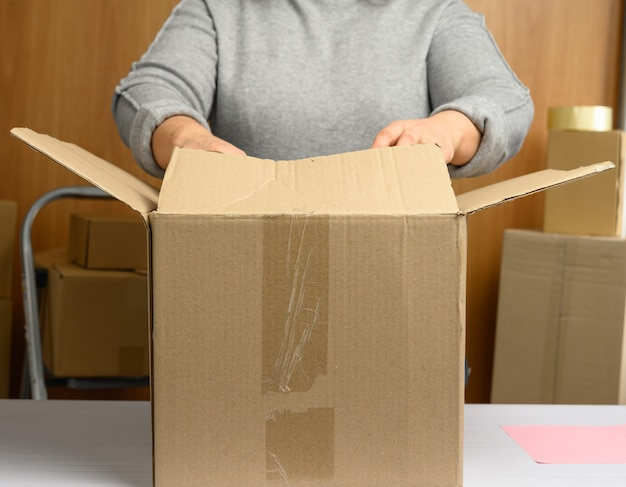 Woman in a gray sweater is packing brown cardboard boxes on a white table, behind a stack of boxes. moving concept