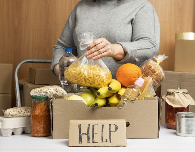 Woman in a gray sweater puts in a cardboard box various foods, fruits, pasta, sunflower oil in a plastic bottle and preserves. donation and volunteering concept