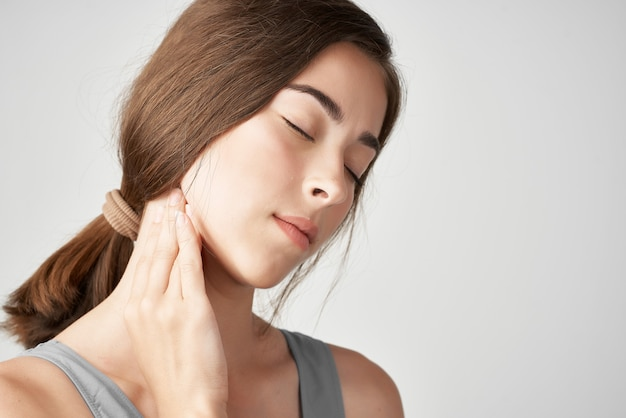 Woman in gray t shirt neck pain discontent health problems