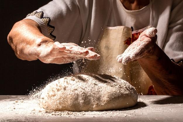 家で焼くために小麦粉の生地で作りたてのペストリーのマウンドをほこりで払うために手をたたく女性の祖母