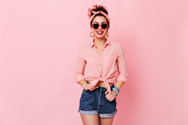 Woman in great mood is posing on pink space. girl in sunglasses and gold earrings dressed in shirt and shorts is smiling.