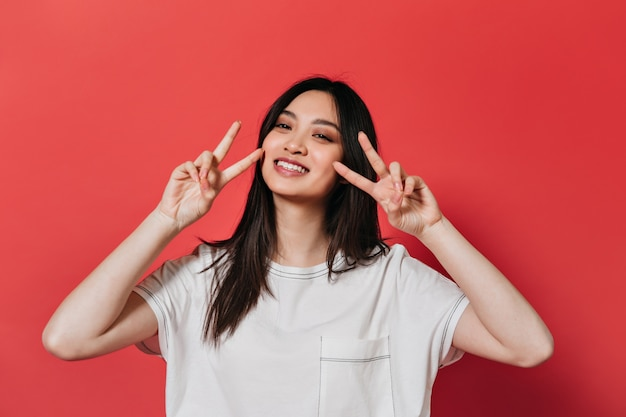 Woman in great mood poses on red wall and shows peace sign