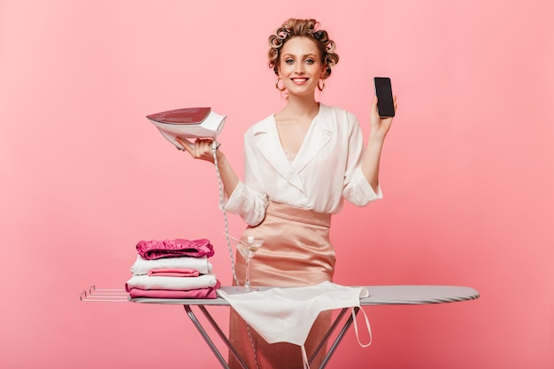 Donna di ottimo umore posa con smartphone e ferro vicino all'asse da stiro