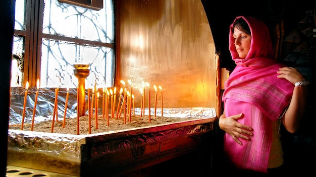 Woman in greek church looking at burning candles