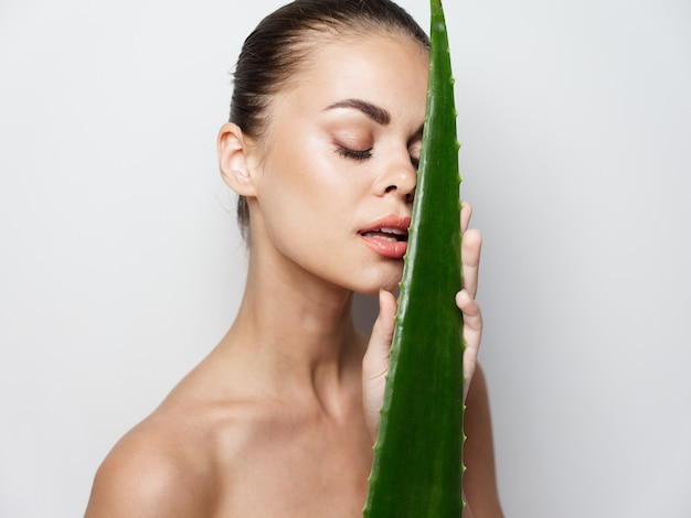 Woman next to a green aloe leaf on a composite plan clean skin cosmetology
