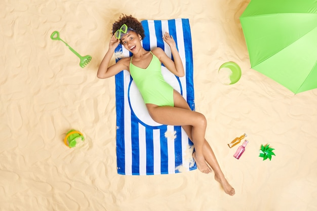 Woman in green bikini lies on towel gets suntan has joyful mood enjoys recreation time summer vacation surrounded by beach toys energetic drinks and parasol