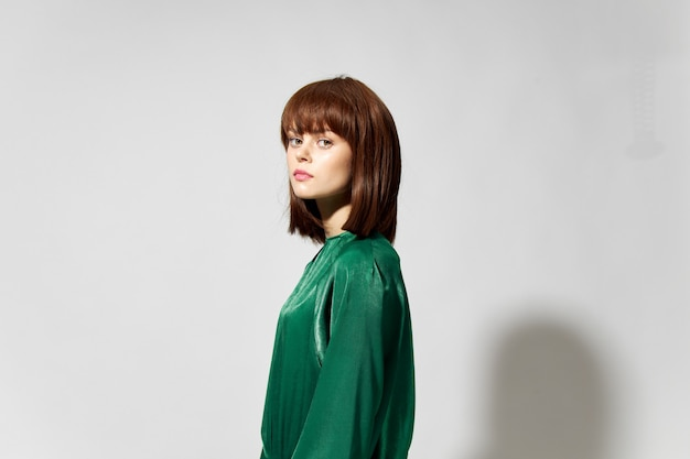 Woman in green fashion dress model with a hairstyle.