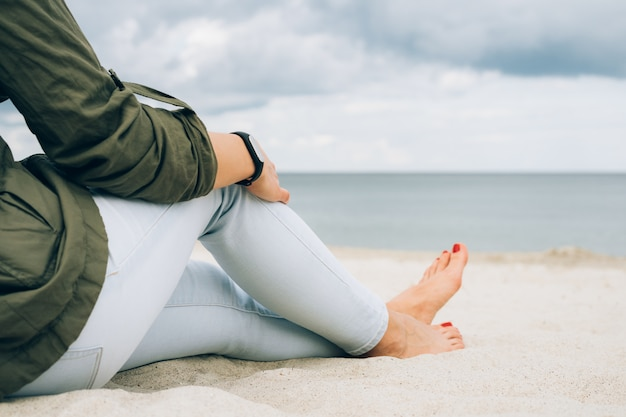 Woman in green jacket and jeans sits on a beach and looks at sea