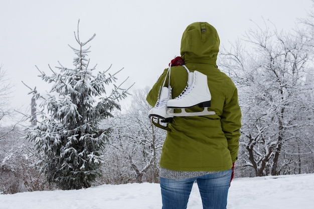 Woman in a green jacket with ice skates looks at the snowy forest