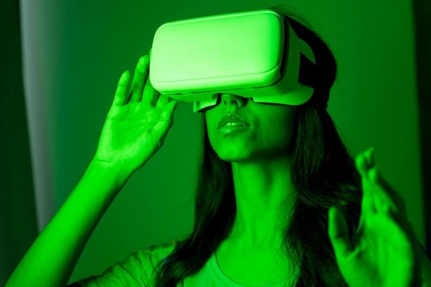 Donna in luce verde utilizzando l'auricolare per realtà virtuale