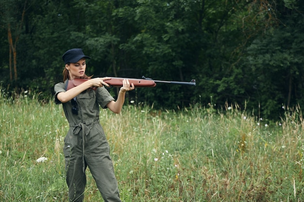 Woman green overalls weapon in the hands of hunting fresh air fresh air cropped view