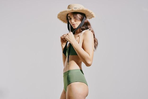 Woman in green swimsuit beach bag fashion summer studio. high quality photo