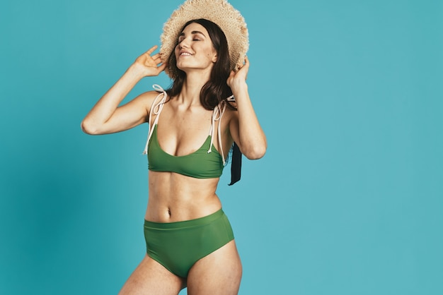 Woman in green swimsuit beach season summer glamor. high quality photo