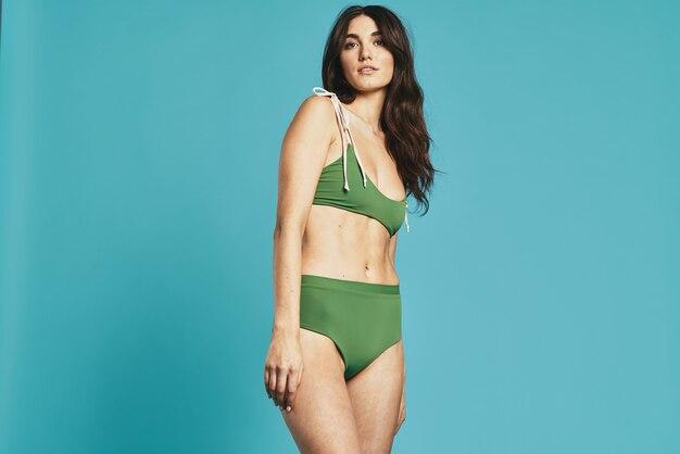 Woman in green swimsuit beach season summer glamor