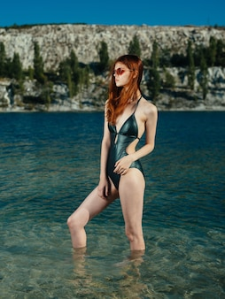 Woman in green swimsuit stands in transparent water river sunglasses model