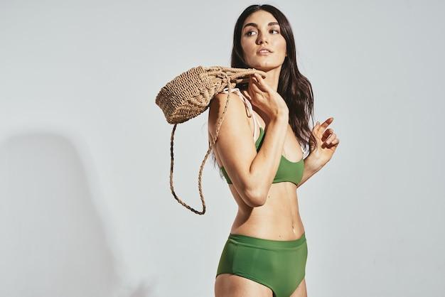 夏のポーズをとる女性の緑の水着ビーチバッグモデル